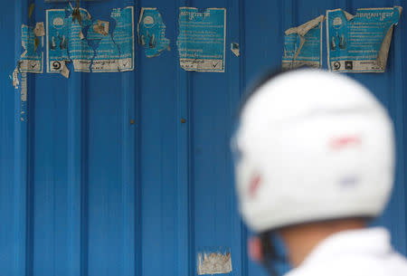 A man stands near posters the Cambodia National Rescue Party on the outskirts of Phnom Penh