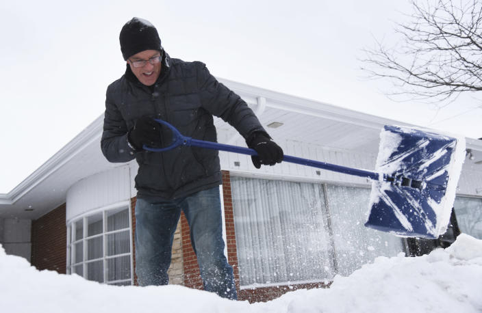 Mike Siri removes snow from in front of The Relationship Center in downtown Wauconda, Ill., Tuesday, Jan. 26, 2021. (Paul Valade/Daily Herald via AP)