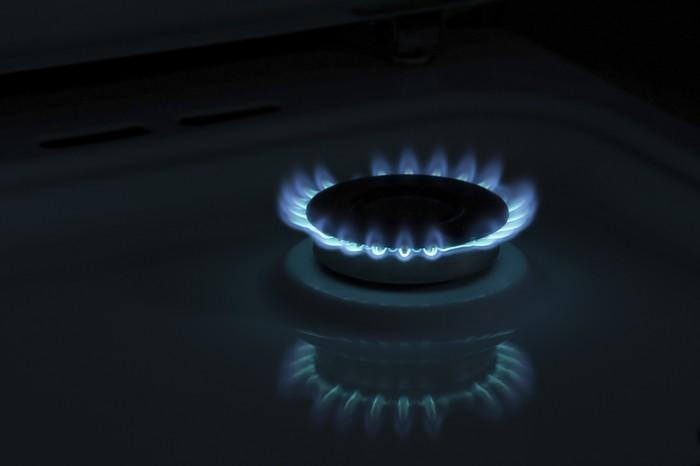 A gas burner emits blue flames.