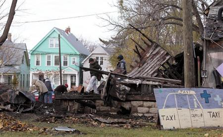 People try to save remains from a vacant house that was covered with hundreds of vinyl LP music albums, known as the 'House of Soul', that is part of the internationally known Heidelberg Project outdoor art installation by artist and founder Tyree Guyton