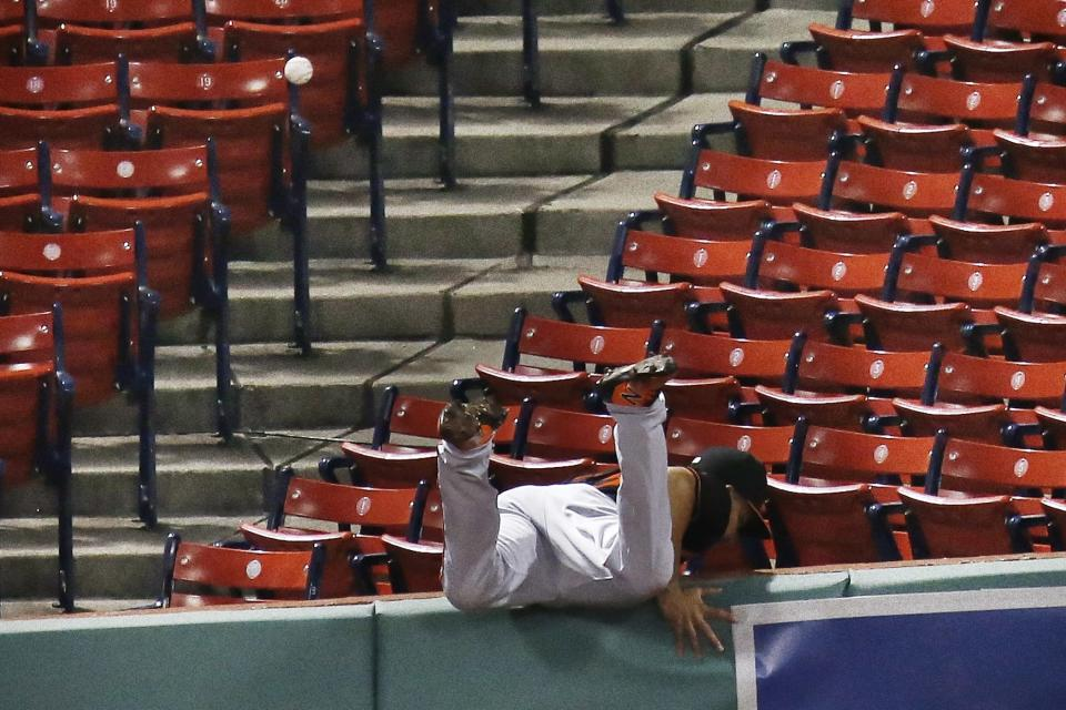 Baltimore Orioles' Anthony Santander goes over the wall trying to field the ground-rule double by J.D. Martinezduring the fourth inning of an opening day baseball game at Fenway Park, Friday, July 24, 2020, in Boston. (AP Photo/Michael Dwyer)