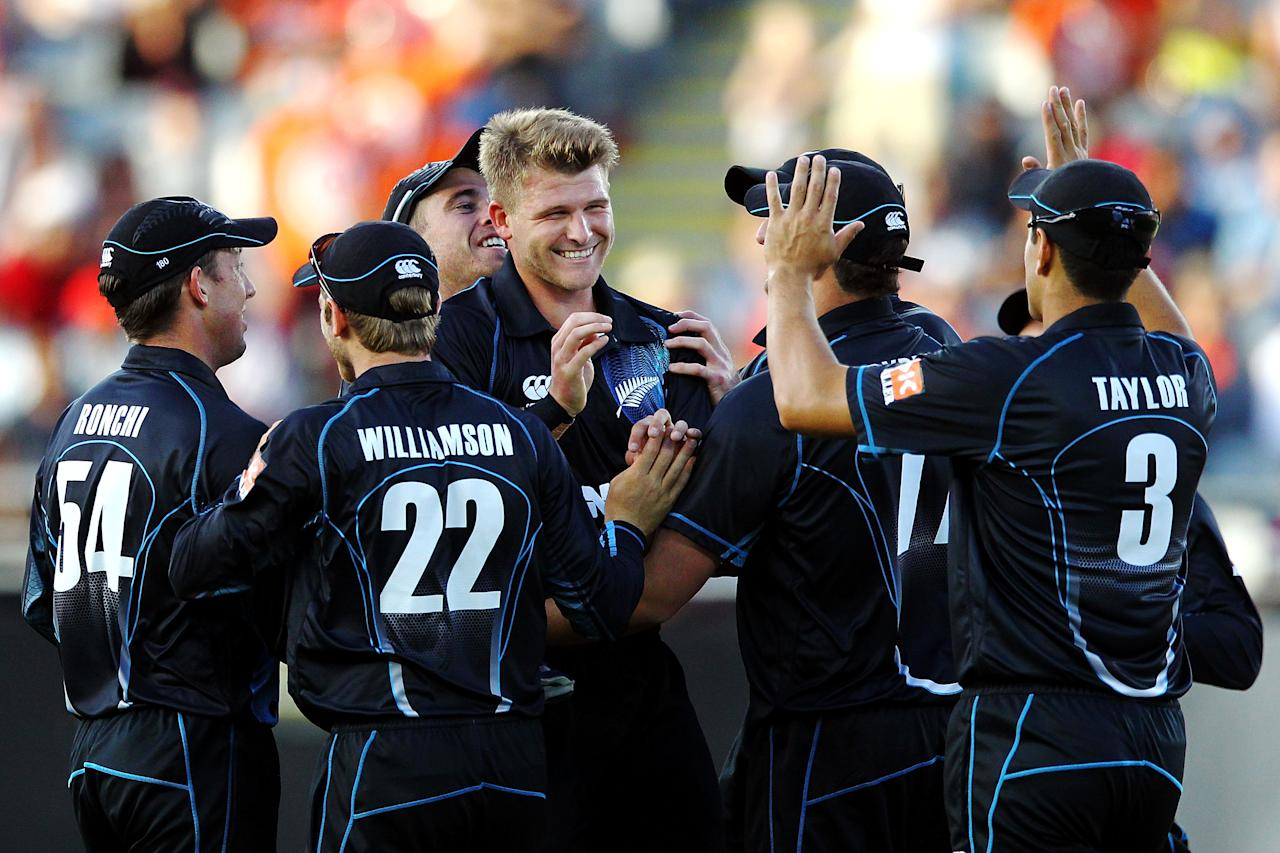 AUCKLAND, NEW ZEALAND - JANUARY 25:  Corey Anderson of New Zealand is mobbed by his teammates after taking the wicket of Ajinkya Rahane of India during the One Day International match between New Zealand and India at Eden Park on January 25, 2014 in Auckland, New Zealand.  (Photo by Anthony Au-Yeung/Getty Images)