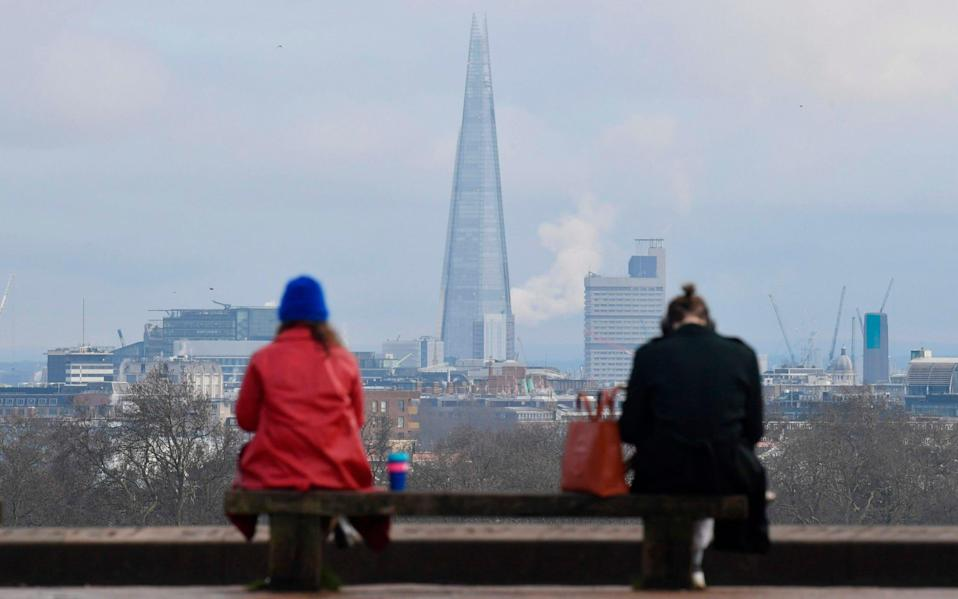 People sit at a social distance from one another on a bench on the top of Primrose Hill in London - JUSTIN TALLIS/AFP