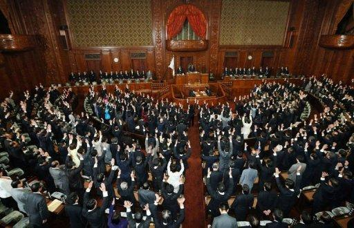 Members of the lower house of parliament raise their hands for banzai cheers at the National Diet in Tokyo as the lower house was dissolved