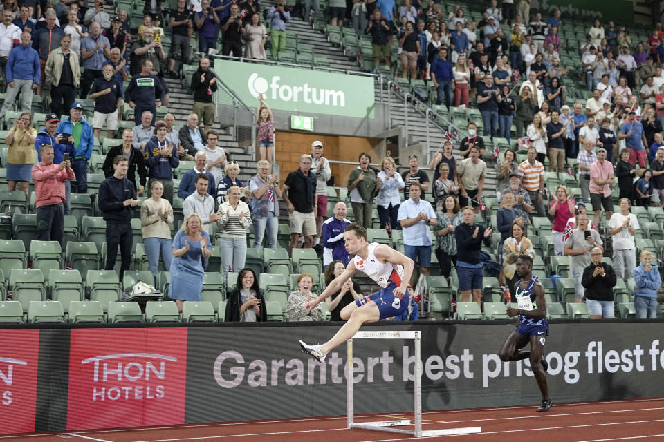 Norway's Karsten Warholm, left, races to win in 46.70 seconds to set a new men's 400m hurdles world record at the Diamond League meeting in Oslo, Norway Thursday July 1, 2021. (Fredrik Hagen, NTB via AP)