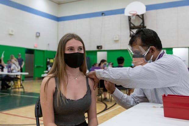 Hannah Duffy, 14, gets her first dose of the Pfizer-BioNTech COVID-19 vaccine at a clinic held at Don Bosco Catholic Secondary School in Toronto.  (Evan Mitsui/CBC - image credit)