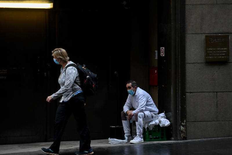 People wear face masks whilst in the central business district of Sydney.