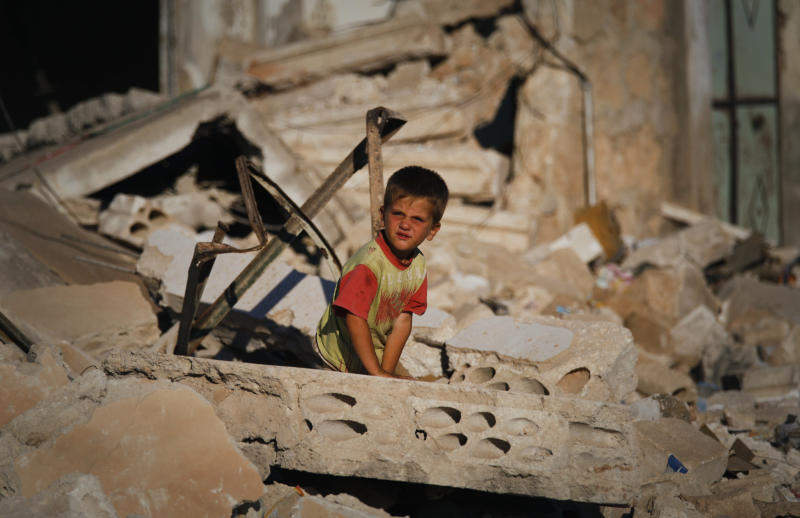 FILE - In a Tuesday, June 5, 2012 file photo, a Syrian boy sits in the rubble of house which was destroyed during a military operation by the Syrian army in April 2012, in the town of Taftanaz, 15 kilometers east of Idlib, Syria. (AP Photo/Khalil Hamra, File)