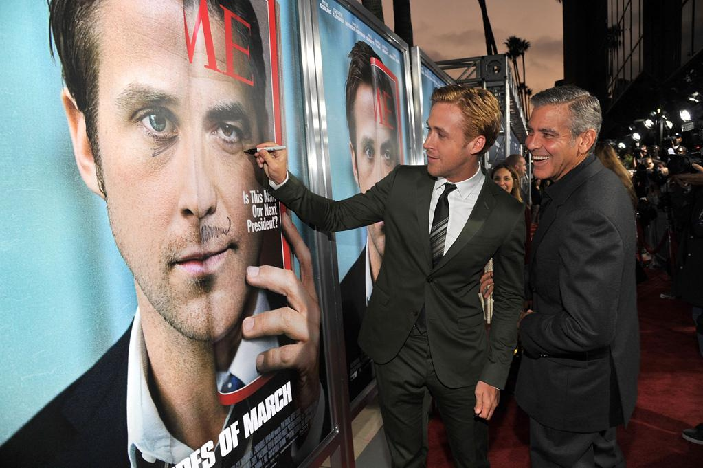 "Hollywood hotties George Clooney and Ryan Gosling got a little goofy, scribbling on a poster of themselves on the red carpet prior to the L.A. premiere of their new flick ""The Ides of March"" in Beverly Hills on Tuesday evening. Have all the fun you want, guys, but don't mess with your <i>real</i> faces. Lester Cohen/<a href=""http://www.wireimage.com"" target=""new"">WireImage.com</a> - September 27, 2011"
