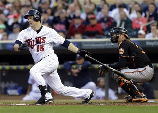 Minnesota Twins' Josh Willingham, left, hits a ground-out RBI in the first inning of a baseball game off Baltimore Orioles pitcher Jason Hammel, Friday, May 10, 2013, in Minneapolis. Orioles catcher Matt Wieters, right, looks on. (AP Photo/Jim Mone)