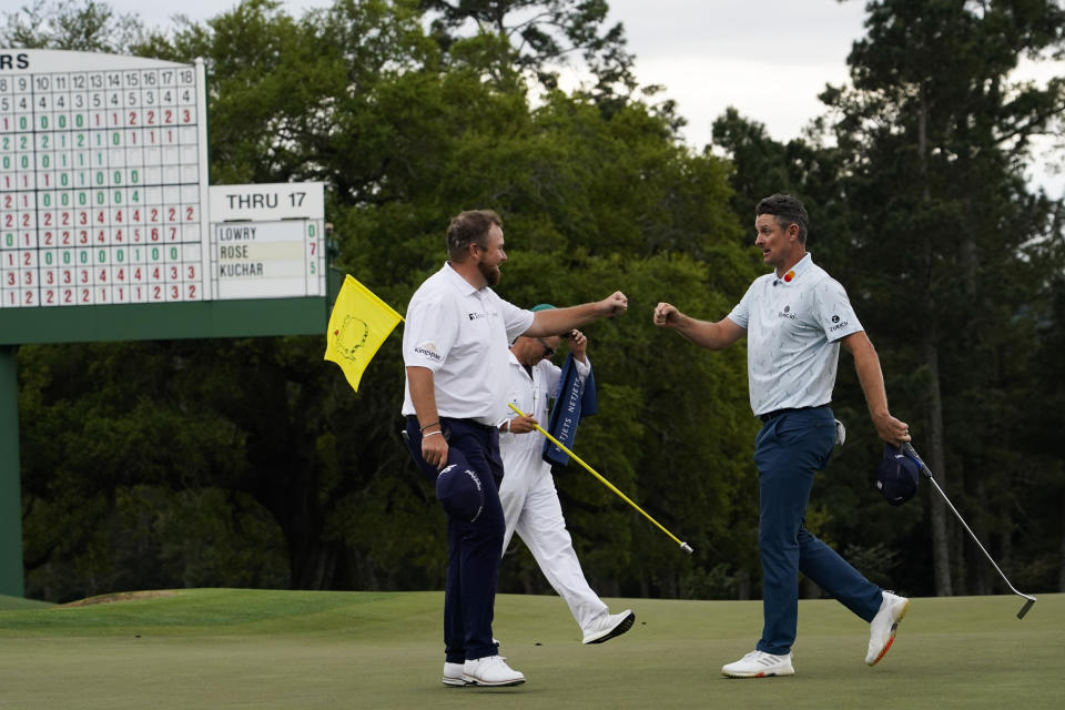 Justin Rose, right, of England, is congratulated by Shane Lowry, of Ireland, on the 18th hole after their first round at the Masters golf tournament on Thursday, April 8, 2021, in Augusta, Ga. (AP Photo/David J. Phillip)