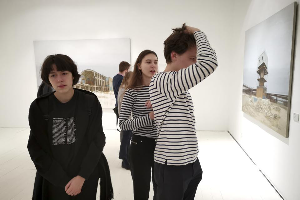 In this photo taken on Sunday, Feb. 17, 2019, visitors attend an exhibition by Russian artist Pavel Otdelnov, in Moscow, Russia . Pavel Otdelnov, a Russian artist who grew up in Dzerzhinsk, the center of the nation's chemical industries 355 kilometers (220 miles) east of Moscow, focused on the city, one of the most polluted in Russia, in his new 'Promzona' art show. (AP Photo/Ivan Kochkarev)
