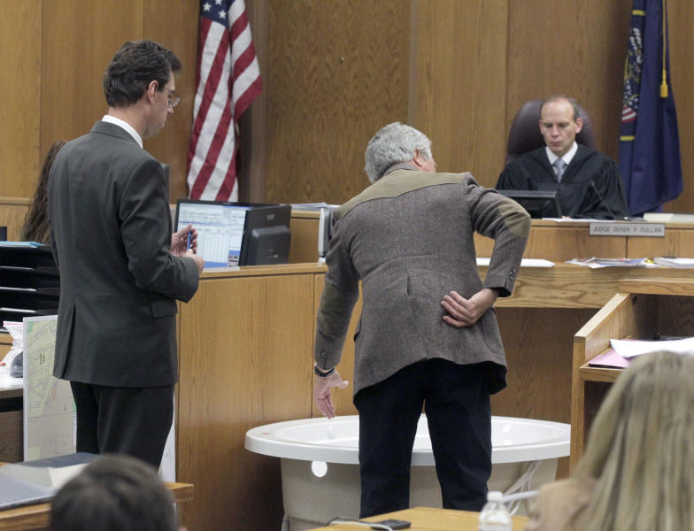 Ergonomics expert Brett Besser, center, testifies at Martin MacNeill's murder trial in 4th District Court in Provo, Utah, Thursday, Nov. 7, 2013. He explains to defense lawyer Randy Spencer, left, stress to lower back and difficulty in lifting a heavy weight from a bathtub. Judge Derek Pullan watches the demonstration. (AP Photo/The Salt Lake Tribune, Al Hartmann, Pool )