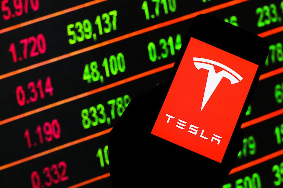 """As Tesla stock climbed, Robinhood users bought. Of Robinhood's most popular stocks, around a third are in this """"momentum trading"""" category. (Photo by Filip Radwanski/SOPA Images/LightRocket via Getty Images)"""