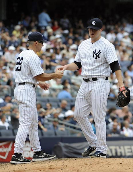 New York Yankees manager Joe Girardi, left, takes New York Yankees starting pitcher Phil Hughes out of the game after Baltimore Orioles' Mark Reynolds hit a three-run home run in the sixth inning of a baseball game on Sunday, Sept. 2, 2012, at Yankee Stadium in New York. (AP Photo/Kathy Kmonicek)