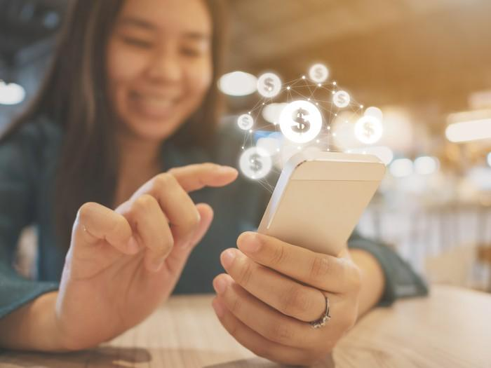 Young woman on mobile phone with dollar signs hovering over the screen.