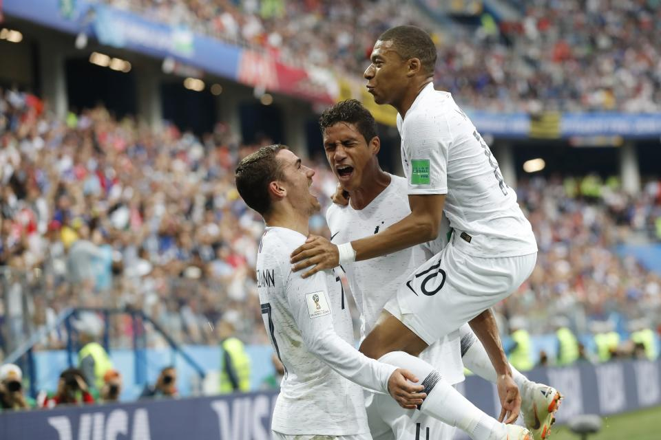 Kylian Mbappe, Antoine Griezmann and Raphael Varane celebrate one of their two goals in France's World Cup quarterfinal victory over Uruguay. (AP)