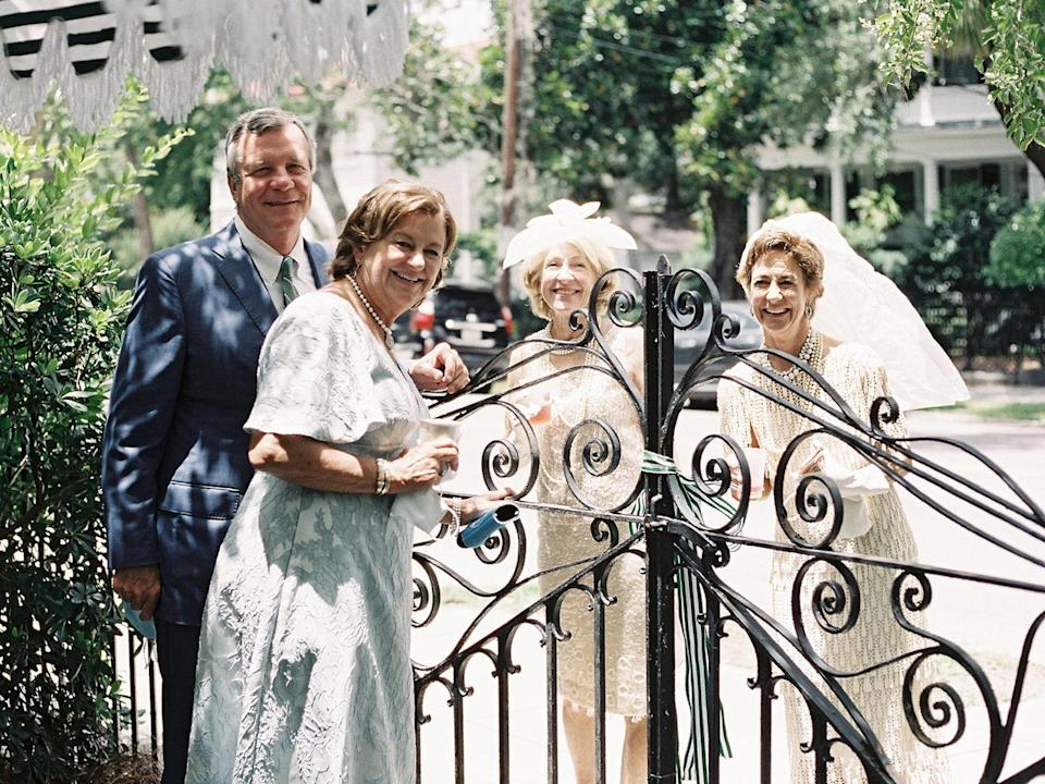 The mother and father of the bride posing with old friends.