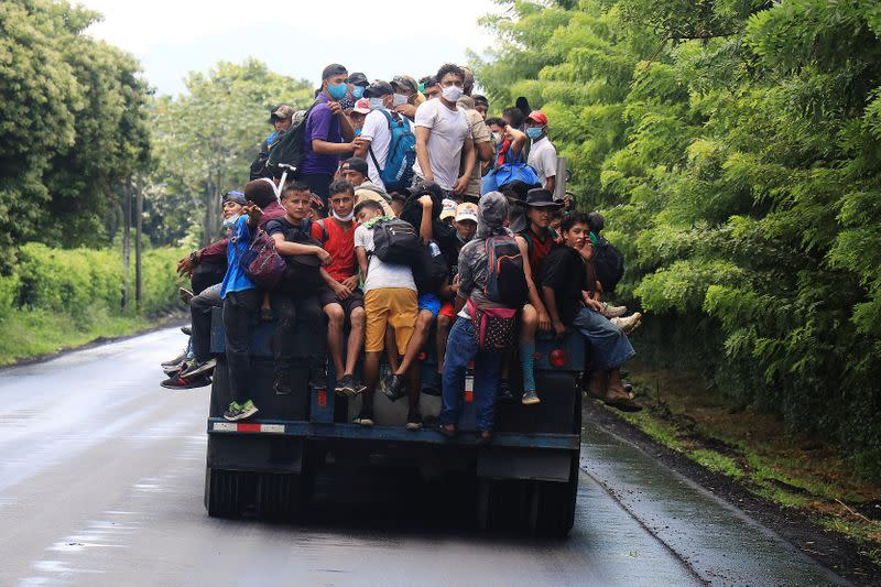 Honduran migrants trying to reach the U.S. hitchhike on a truck after bursting through a border checkpoint to enter Guatemala illegally, in Entre Rios