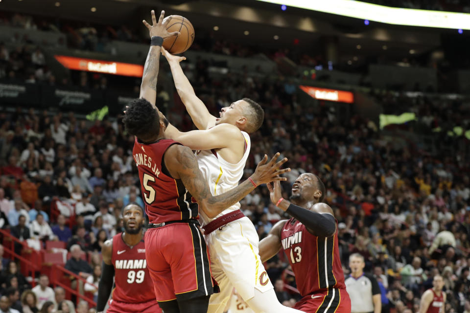 Cleveland Cavaliers guard Dante Exum, center, goes up to shoot against Miami Heat forwards Derrick Jones Jr. (5) and Bam Adebayo (13) during the first half of an NBA basketball game, Saturday, Feb. 22, 2020, in Miami. (AP Photo/Wilfredo Lee)