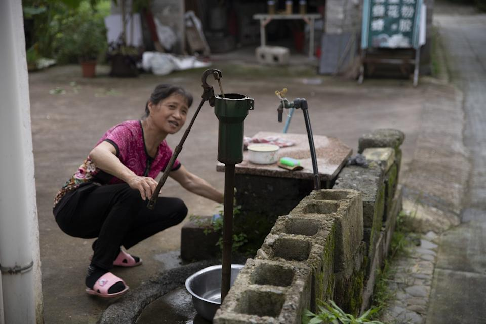 "A villager pumps water from a well in Xixinan village, Anhui province. Urbanization and industrial pollution have severely affected groundwater in China — 80% of it is unsafe for consumption, and without better methods of rainwater absorption, the levels are dropping every year. <span class=""copyright"">(Liu Bowen / For The Times)</span>"
