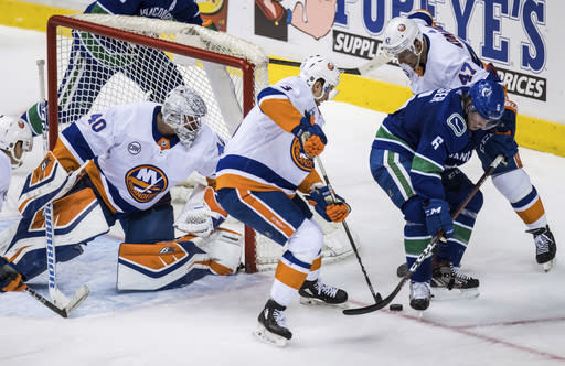Vancouver Canucks' Brock Boeser (6) is checked by New York Islanders' Leo Komarov (47), of Finland, and Adam Pelech (3) as goalie Robin Lehner watches during the second period of an NHL hockey game Saturday, Feb. 23, 2019, in Vancouver, British Columbia. (Darryl Dyck/The Canadian Press via AP)