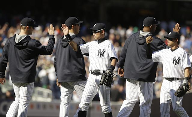 New York Yankees' Ichiro Suzuki, of Japan, center, and Brian Roberts, right, celebrate with teammates after their 7-4 over the Boston Red Sox in a baseball game Saturday, April 12, 2014, in New York. (AP Photo/Frank Franklin II)