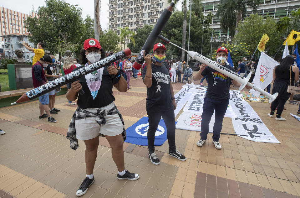 Demonstrators holding fake guns shaped like pencils, and a syringe, attend a protest against Brazilian President Jair Bolsonaro and his handling of the pandemic and economic policies protesters say harm the interests of the poor and working class, in Cuiaba, Brazil, Saturday, June 19, 2021. (AP Photo/Andre Penner)