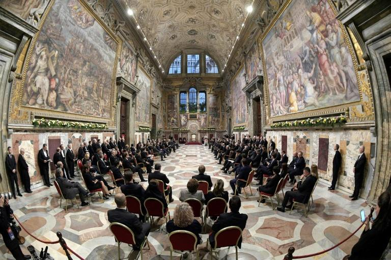 Pope Francis (background) speaks to an audience with 27 heads of State or government at the Vatican, on March 24, 2017