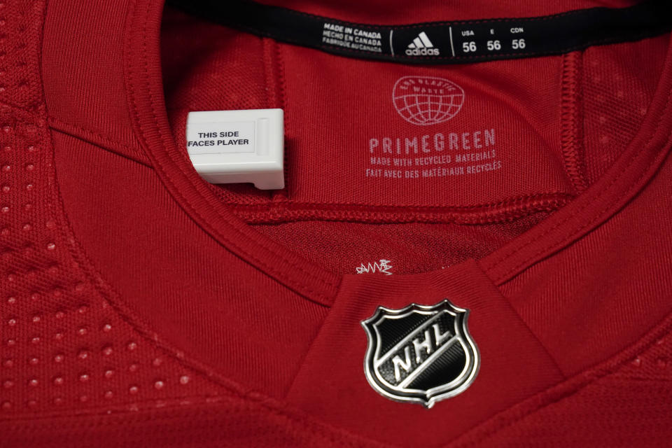 A sensor is shown in a Detroit Red Wings NHL hockey jersey, Tuesday, Oct. 5, 2021, in Detroit. The NHL is using real-time tracking technology in pucks and on the back of players' jerseys, shooting to generate more data for teams, broadcasters, fans and gamblers. (AP Photo/Paul Sancya)