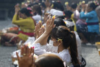 A woman wearing a face mask as a precaution against the new coronavirus outbreak during a Hindu ritual prayer at a temple in Bali, Indonesia on Wednesday, Sept. 16, 2020. (AP Photo/Firdia Lisnawati)