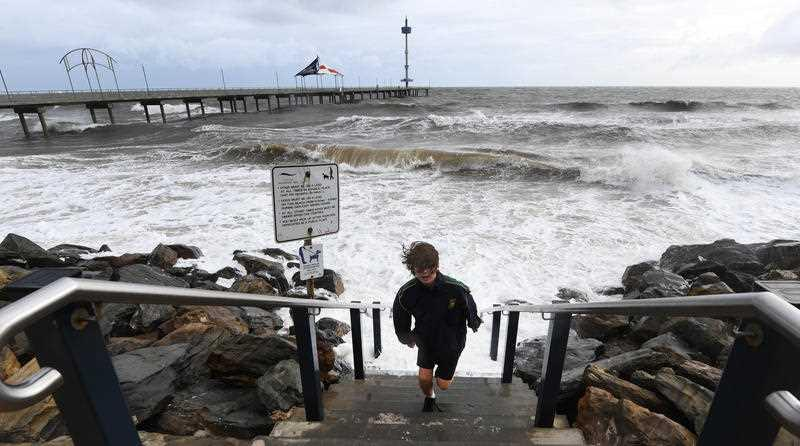 A young boy runs up steps to avoid a wave as high tide and a storm surge at Brighton Jetty as a storm front starts to hit Adelaide's coast line.