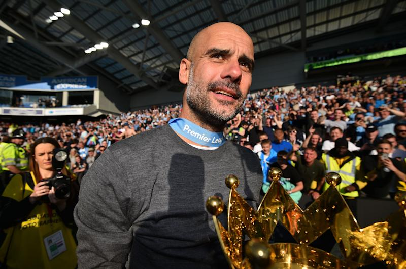 Manchester City's Spanish manager Pep Guardiola shows the Premier League trophy to supporters after their 4-1 victory in the English Premier League football match between Brighton and Hove Albion and Manchester City at the American Express Community Stadium in Brighton, southern England on May 12, 2019. - Manchester City held off a titanic challenge from Liverpool to become the first side in a decade to retain the Premier League on Sunday by coming from behind to beat Brighton 4-1 on Sunday. (Photo by Glyn KIRK / AFP) / RESTRICTED TO EDITORIAL USE. No use with unauthorized audio, video, data, fixture lists, club/league logos or 'live' services. Online in-match use limited to 120 images. An additional 40 images may be used in extra time. No video emulation. Social media in-match use limited to 120 images. An additional 40 images may be used in extra time. No use in betting publications, games or single club/league/player publications. / (Photo credit should read GLYN KIRK/AFP/Getty Images)
