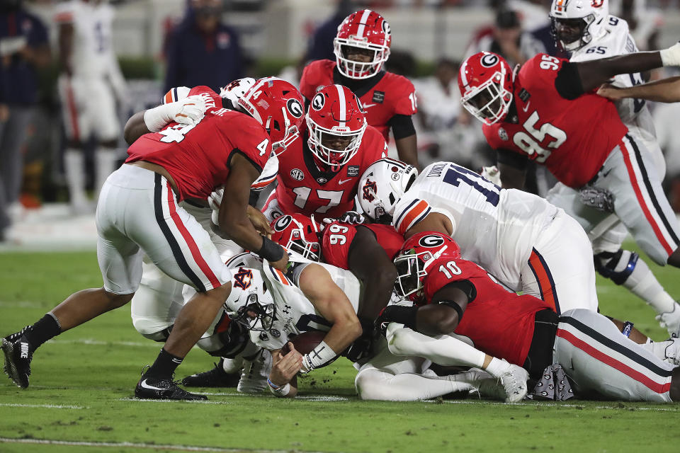 Georgia defenders pile on Auburn quarterback Bo Nix for no gain during the first half of an NCAA college football game Saturday, Oct. 3, 2020, in Athens, Ga. (Curtis Compton/Atlanta Journal-Constitution via AP)