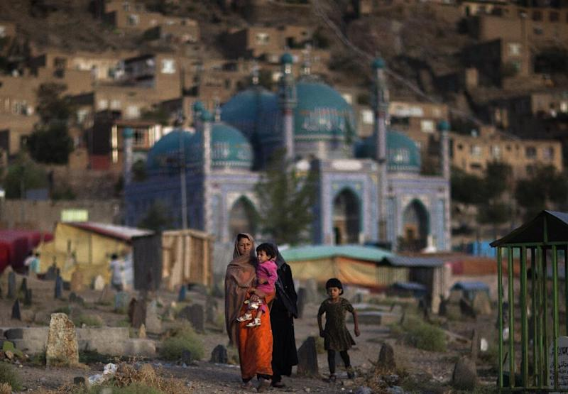 An Afghan woman carries her child through the Kati Sakhi cemetery in Kabul, Afghanistan, Thursday, Sept. 20, 2012. (AP Photo/Dusan Vranic)