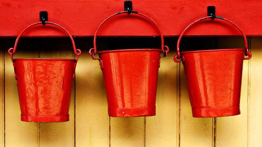 Three red buckets hang on pegs.