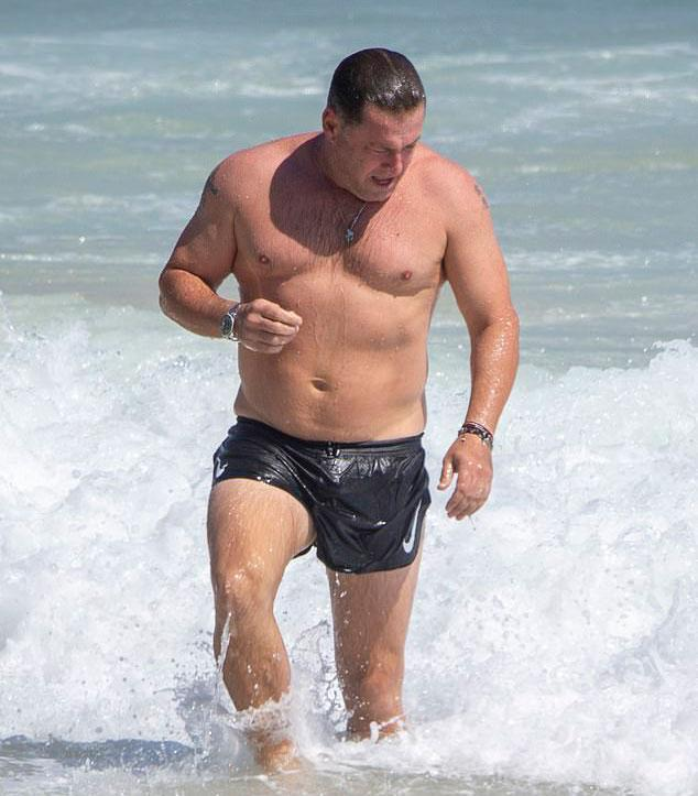 Karl Stefanovic in black swimshorts coming out of the water in Byron Bay