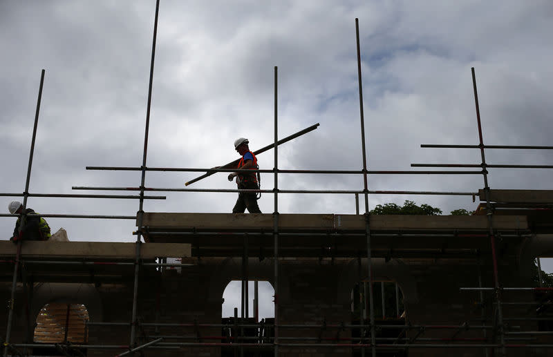 A builder assembles scaffolding as he works on new homes in south London