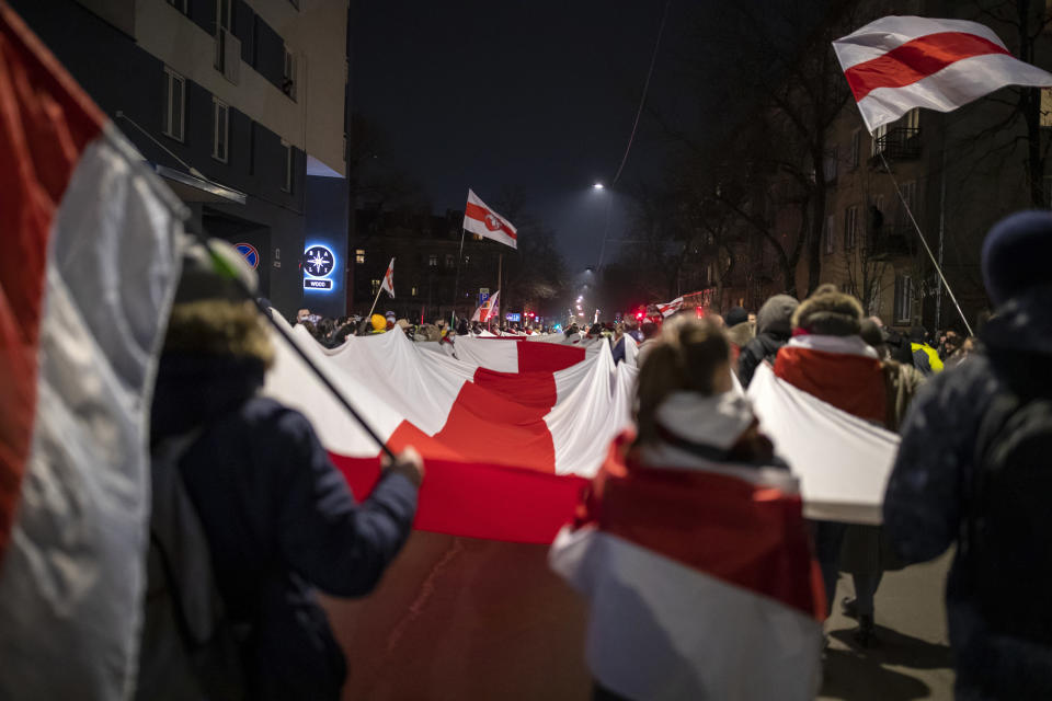 Belarusian people carry a giant historical flag of Belarus during a celebration for the 103rd anniversary of the declaration of the Belarusian People's Respublic, in Vilnius, Lithuania, Thursday, March 25, 2021. Freedom Day is an unofficial holiday in Belarus celebrated on 25 March to commemorate the declaration of independence by the Belarusian Democratic Republic on that date in 1918.(AP Photo/Mindaugas Kulbis)