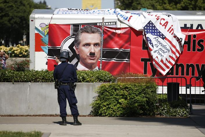 A protest sign against Gov. Gavin Newsom on the side of a truck outside the state Capitol