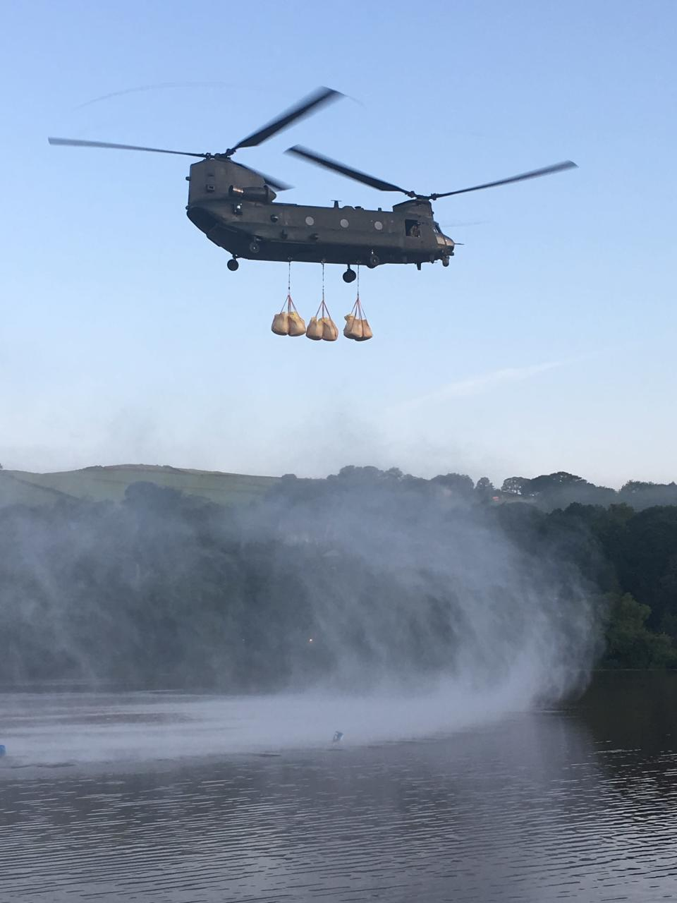 """In this image released by the Ministry of Defence, an RAF Chinook helicopter flies in sandbags to help repair the dam at Toddbrook reservoir near the village of Whaley Bridge in Derbyshire, England, Friday, Aug. 2, 2019. A British military helicopter dropped sandbags Friday to shore up a reservoir wall as emergency services worked frantically to prevent a rain-damaged dam from collapsing. Engineers said they remain """"very concerned"""" about the integrity of the 19th-century Toddbrook Reservoir, which contains around 1.3 million metric tons (1.5 million (U.S tons) of water. (Gary Lane/Ministry of Defence via AP)"""