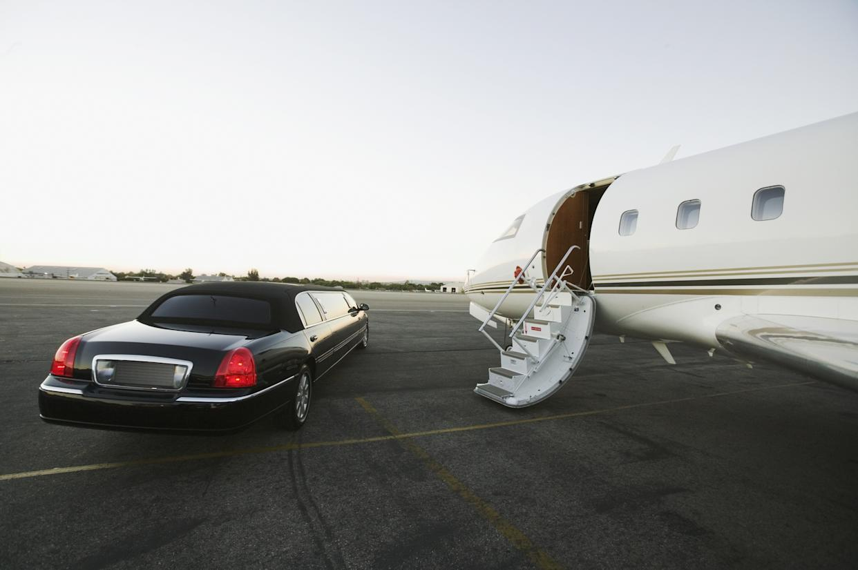 Stretch limo parked beside airplane