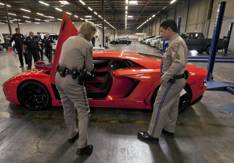 """California Highway Patrol officers: Lt. Glenda Brents, left, and Sgt. Mike Stefanoff, check the vin number of an intercepted 2012 Lamborghini Aventador LP700-4 """"supercar,"""" that was being illegally exported with a lesser declared value, being held by U.S. Customs and Border Protection, next to other 20 high-end stolen vehicles that were intercepted on their way to Honk Kong and Vietnam, in Carson, Calif., on Tuesday, April 3, 2012. (AP Photo/Damian Dovarganes)"""