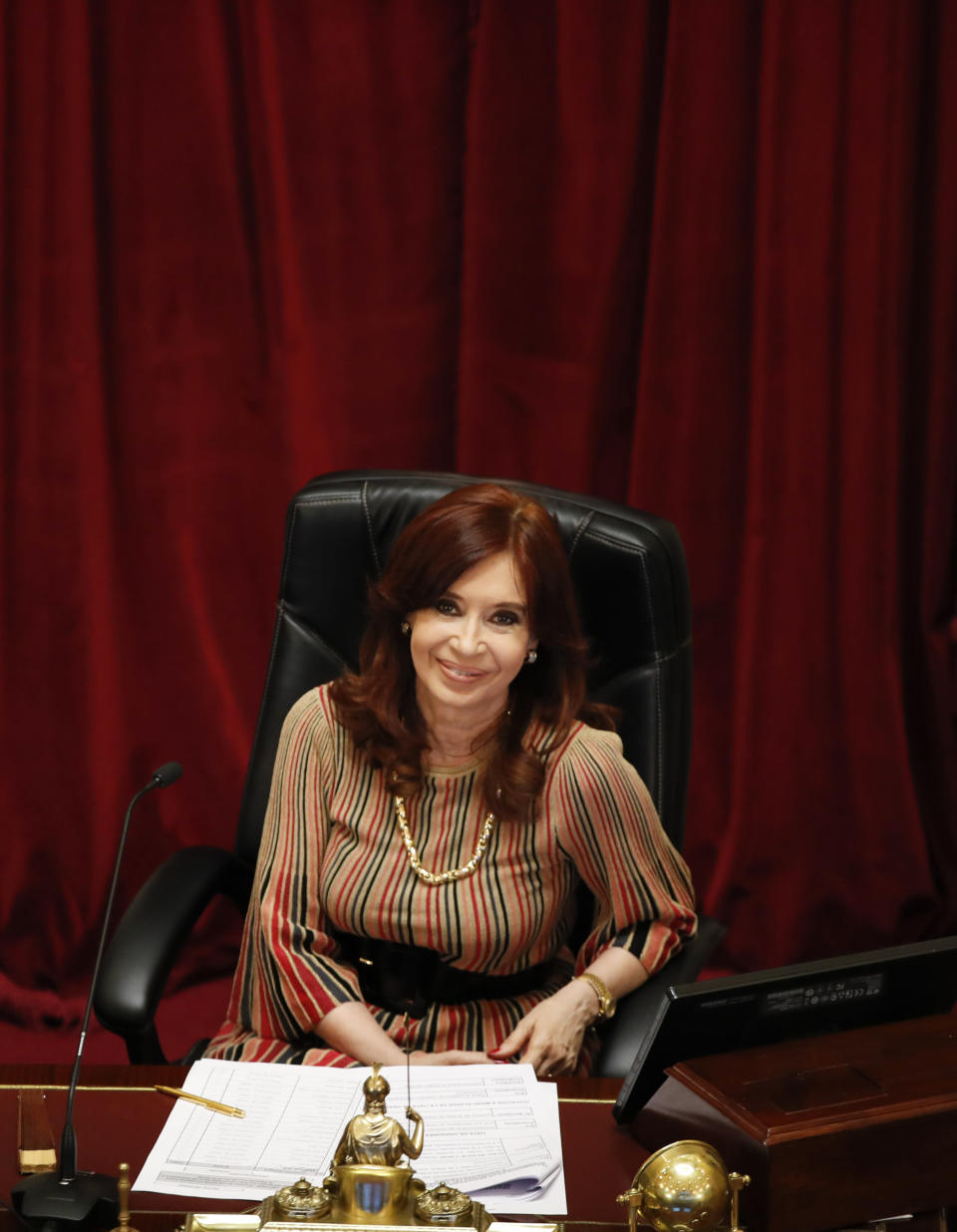 Senate President and Argentina's Vice President Cristina Fernandez smiles during the debate of a bill that would legalize abortion, inside Congress in Buenos Aires, Argentina, Tuesday, Dec. 29, 2020. (AP Photo/Natacha Pisarenko)