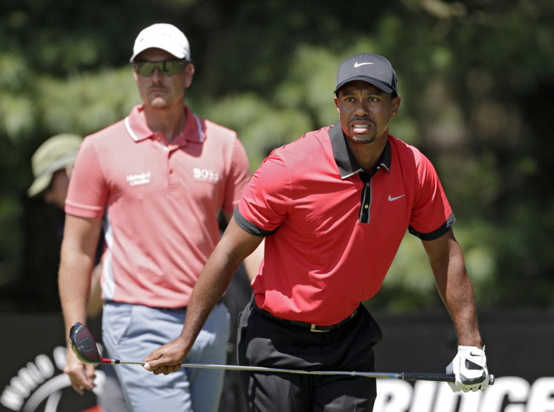 Tiger Woods watches his tee shot on the second hole with Henrik Stenson, from Sweden, left, during the final round of the Bridgestone Invitational golf tournament Sunday, Aug. 4, 2013 at Firestone Country Club in Akron, Ohio. (AP Photo/Mark Duncan)