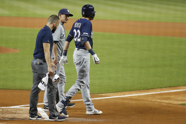 Milwaukee Brewers' Christian Yelich (22) walks off the field with a trainer and manager Craig Counsell, center, after an injury during the first inning of the team's baseball game against the Miami Marlins, Tuesday, Sept. 10, 2019, in Miami. Yelich broke his right kneecap on a foul ball and will miss the rest of the regular season. (AP Photo/Wilfredo Lee)