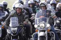 """FILE - In this May 9, 2021 file photo, Brazil's President Jair Bolsoanro, left, takes a motorcycle tour with supporters representing the moto clubs in honor of Mother's Day, in Brasilia, Brazil. Bolsonaro has waged a 15-month campaign to downplay the virus's seriousness and keep the economy humming, dismissing the pandemic early on as """"a little flu"""" and has scorned masks. (AP Photo/Eraldo Peres, File)"""