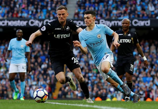 "Soccer Football - Premier League - Manchester City v Swansea City - Etihad Stadium, Manchester, Britain - April 22, 2018 Manchester City's Phil Foden in action with Swansea City's Andy King REUTERS/Phil Noble EDITORIAL USE ONLY. No use with unauthorized audio, video, data, fixture lists, club/league logos or ""live"" services. Online in-match use limited to 75 images, no video emulation. No use in betting, games or single club/league/player publications. Please contact your account representative for further details."
