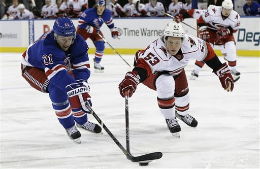 New York Rangers' Derek Stepan (21) and Carolina Hurricanes' Jeff Skinner (53) fight for control of the puck during the second period of an NHL hockey game, Monday, March 18, 2013, in New York. (AP Photo/Frank Franklin II)