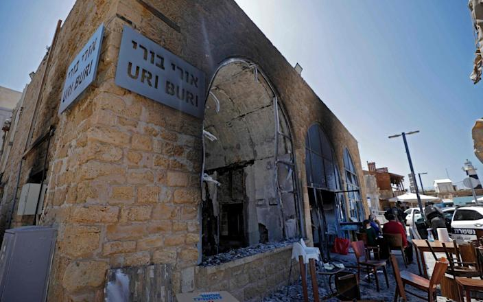 A picture taken in Acre, a mixed Arab-Jewish town in northwest Israel, shows the Uri Buri restaurant after it was attacked and burned by Arab extremists - AFP